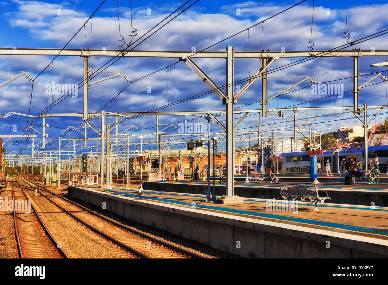 Platforms of Redfern train station in Greater Sydney with daily commuters and city visitors boarding and aligting from the train on open platform unde - Stock Image