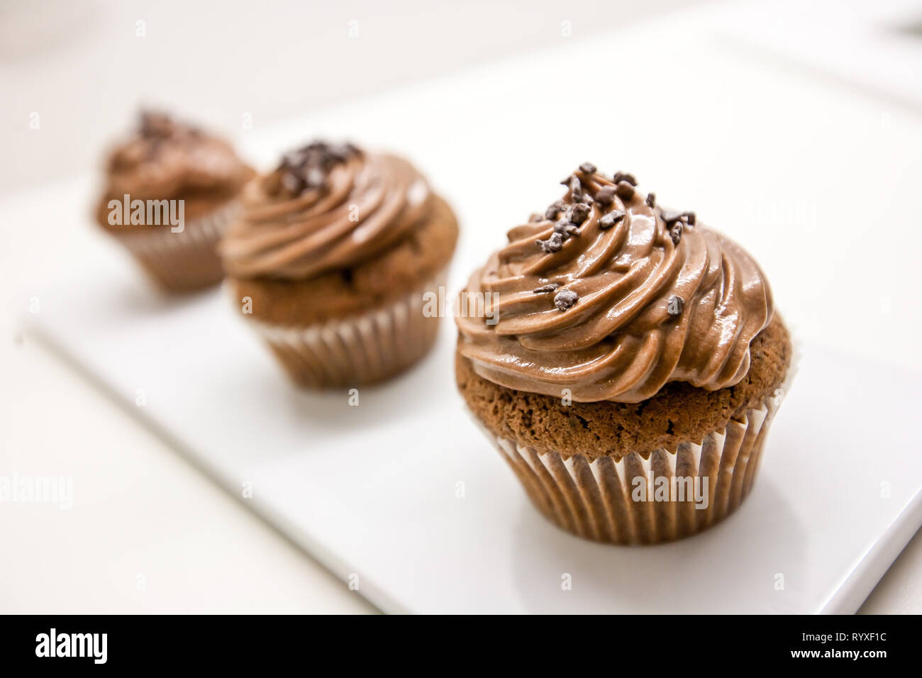 Home made chocolate cupcakes on white plate and table Stock Photo