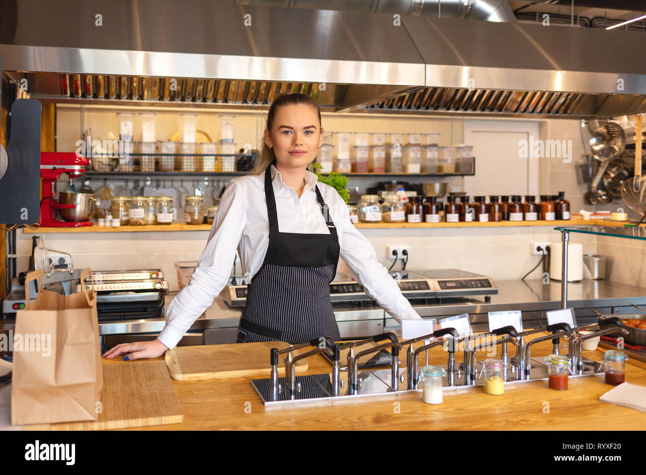 Portrait of young woman standing behind kitchen counter in small eatery – restaurant owner wearing apron looking confident at camera smiling - Stock Image