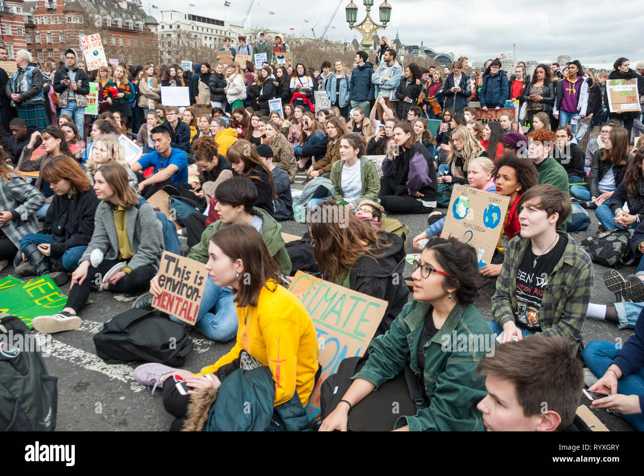 London, UK. 15th March, 2019. School students campaigning against climate change protest outside Parliament. Credit: Maggie sully/Alamy Live News. School children on strike to protest at climate change gather outside Parliament, London, and have a sit down protest on Westminster Bridge blocking it to all through traffic. There was then a lively meeting with many young speakers addressing the concerns of the youth about climate justice and global warming. Banners include 'This is environ- MENTAL'.  Part of the worldwide 'FridaysforFuture' protest. - Stock Image
