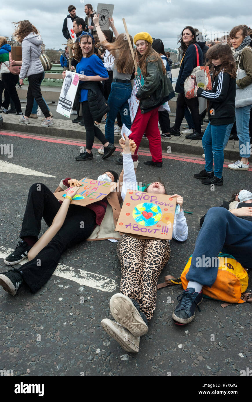 London, UK. 15th March, 2019. School students campaigning against climate change protest outside Parliament. Credit: Maggie sully/Alamy Live News. School children on strike to protest at climate change gathering outside Parliament and on Westminster bridge London.  Some students lay down on Westminster Bridge while others march by with placards. Part of the worldwide 'FridaysforFuture' protest. - Stock Image