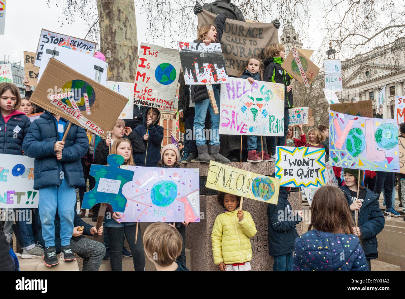 London, UK. 15th March, 2019. School students campaigning against climate change protest outside Parliament. Credit: Maggie sully/Alamy Live News. School children on strike protest at climate change gathering in a lively rally outside Parliament, London. Many small girls and boys with colourful homemade banners and placards 'Help save the planet', 'I won't be quiet', 'This is my life', 'Save our home', among others, as they sing and shout their protests about the destruction of the planet - Stock Image