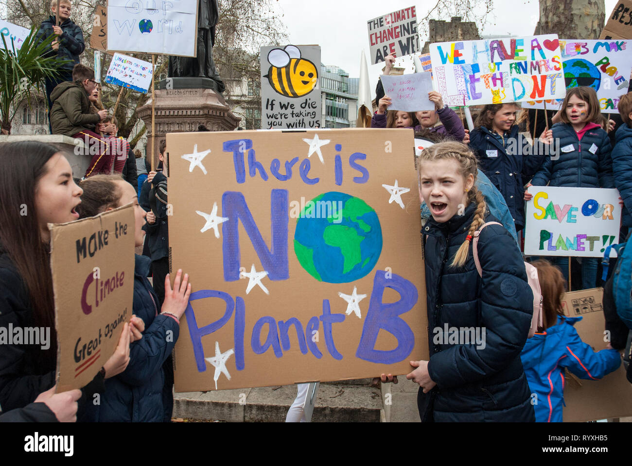 London, UK. 15th March, 2019. School students campaigning against climate change protest outside Parliament. Credit: Maggie sully/Alamy Live News. School children on strike, part of the 'FridaysforFuture' protest against climate change gather outside Parliament, London. Girls shouting slogans about planet justice and global warming carrying a colourful placard 'There is no planet B' with others posters in the background including one with a yellow stripey bee 'If we die we are taking you with us' and 'Save the planet'. - Stock Image