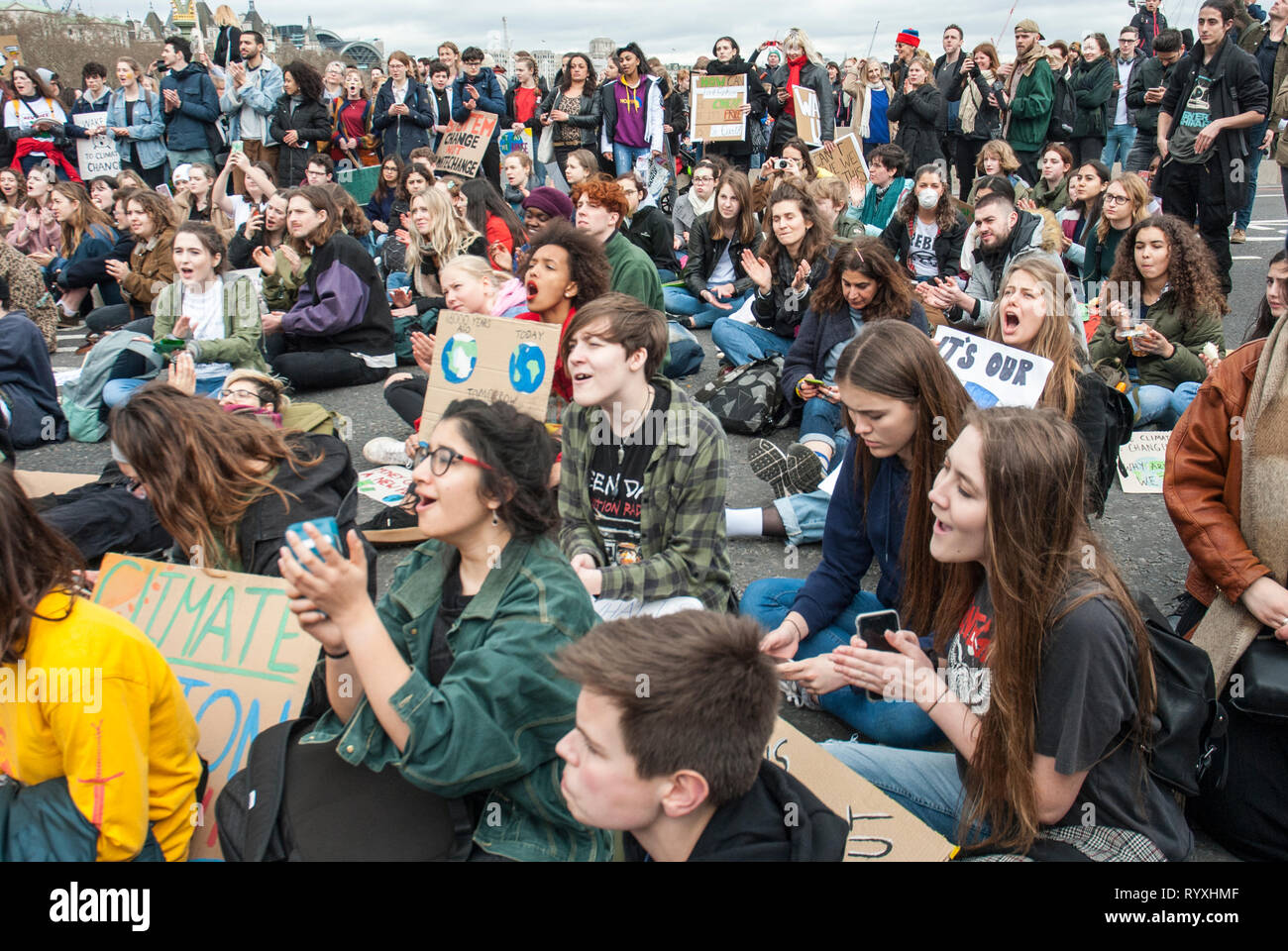 London, UK. 15th March, 2019. School students campaigning against climate change block Westminster Bridge Credit: Maggie sully/Alamy Live News. School children on strike, part of the 'FridaysforFuture' protest against climate change gather outside Parliament, London, and have a sit down protest on Westminster Bridge blocking it to all through traffic. There was then a lively meeting with many young speakers addressing the concerns of the youth about climate justice and global warming. - Stock Image