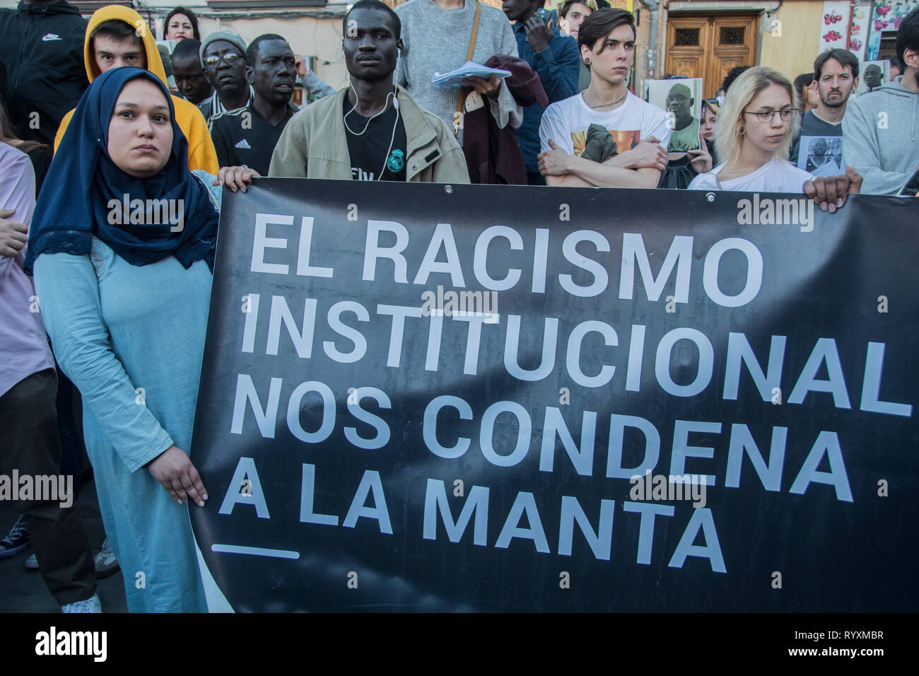 Madrid, Spain. 15th Mar 2019. A woman with a placard ¨Institutional racism condemns us and kills us¨ in the Nelson Mandela square.   March to commemorate one year of the death of senegalese vendor Mmame Mbage in Lavapies Square Nelson Mandela. one year ago there was a clashes between police and immigrants after Mmame Mbage, a Senegalese street vendor, died of a cardiac arrest allegedly after being chased by local police. Credit: Alberto Sibaja Ramírez/Alamy Live News - Stock Image