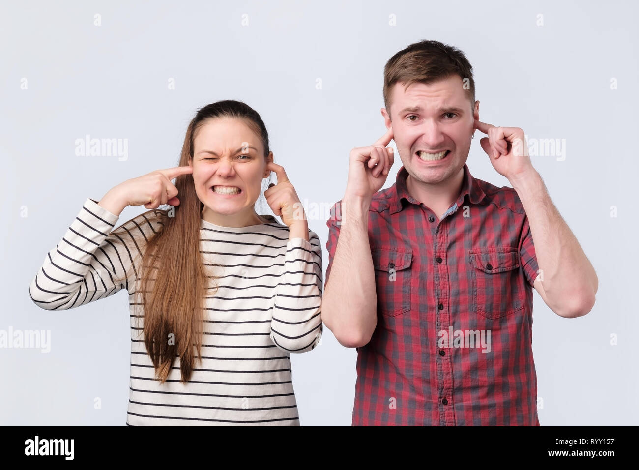 European young family couple woman and man closing ears because of unpleasant loud noise. - Stock Image