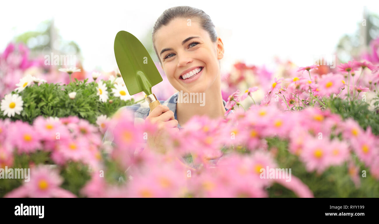 smiling woman in garden of flowers with garden tools, spring concept Stock Photo