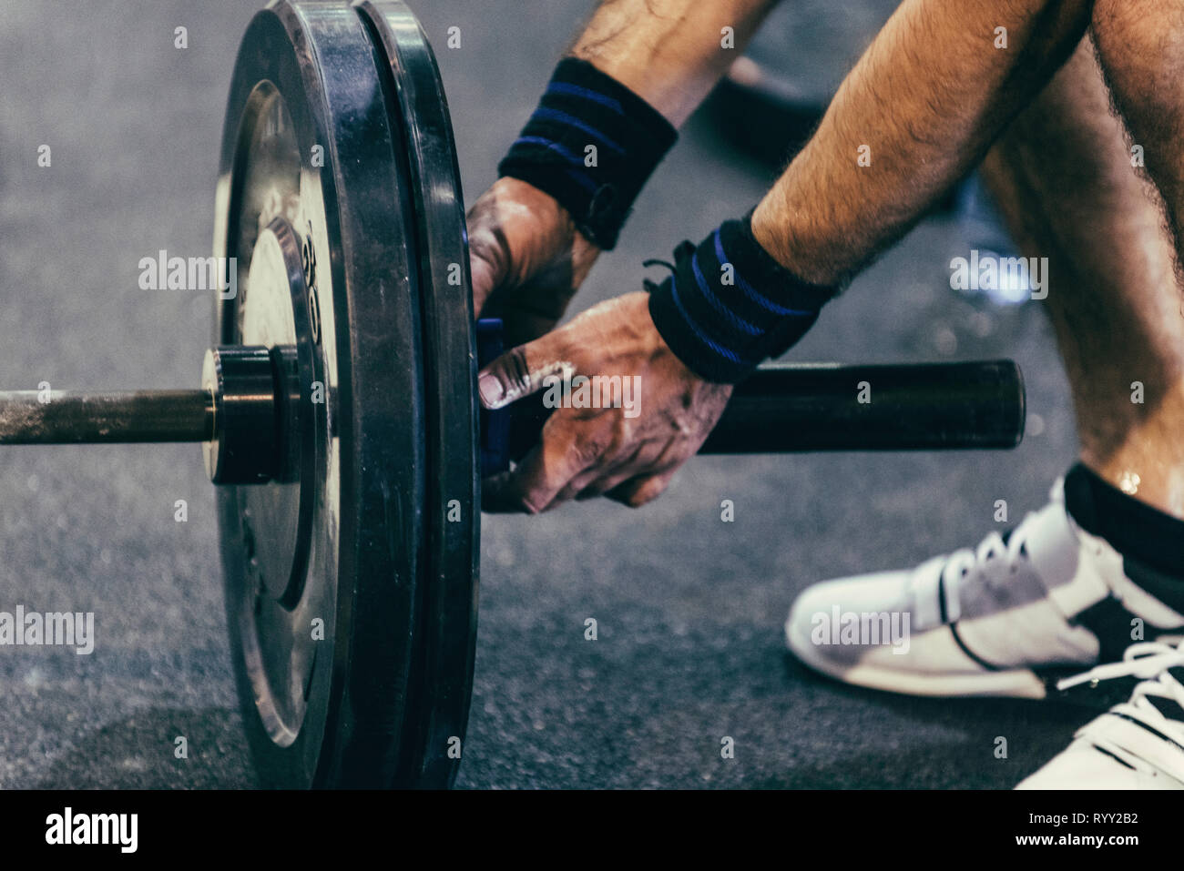 Changing weights on barbell. - Stock Image
