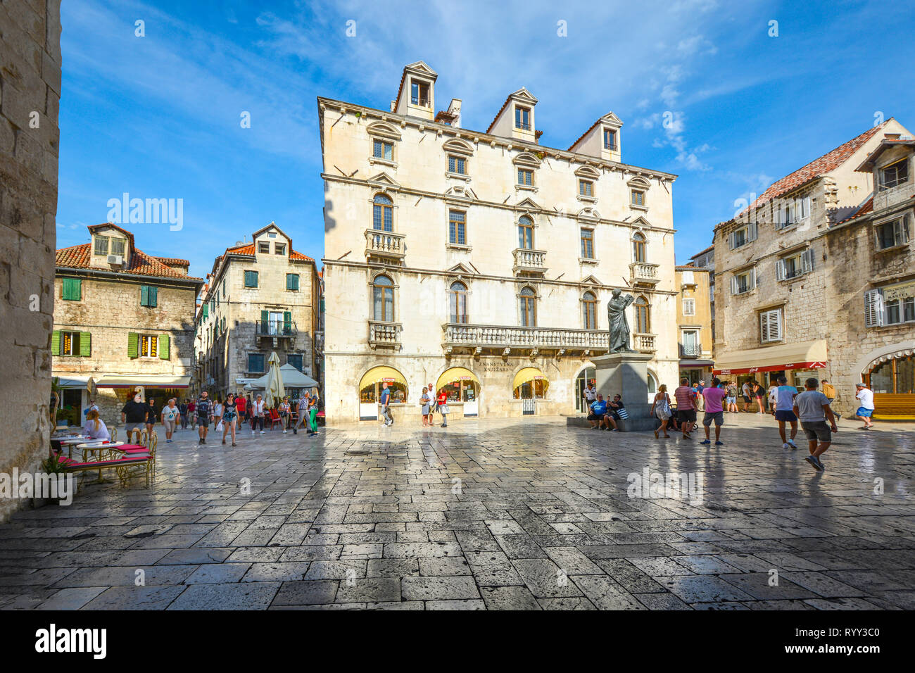 Visitors pass through Trg Brace Radic or the Fruit Square with shops and outdoor cafes on a sunny summer day in Split Croatia Stock Photo