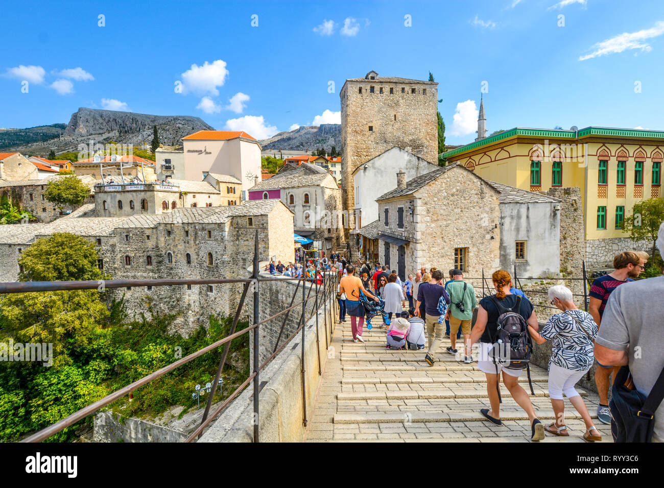 A crowd of tourists cross over the restored Mostar Bridge in the city of Mostar, Bosnia, as they make their way into the old town section. - Stock Image