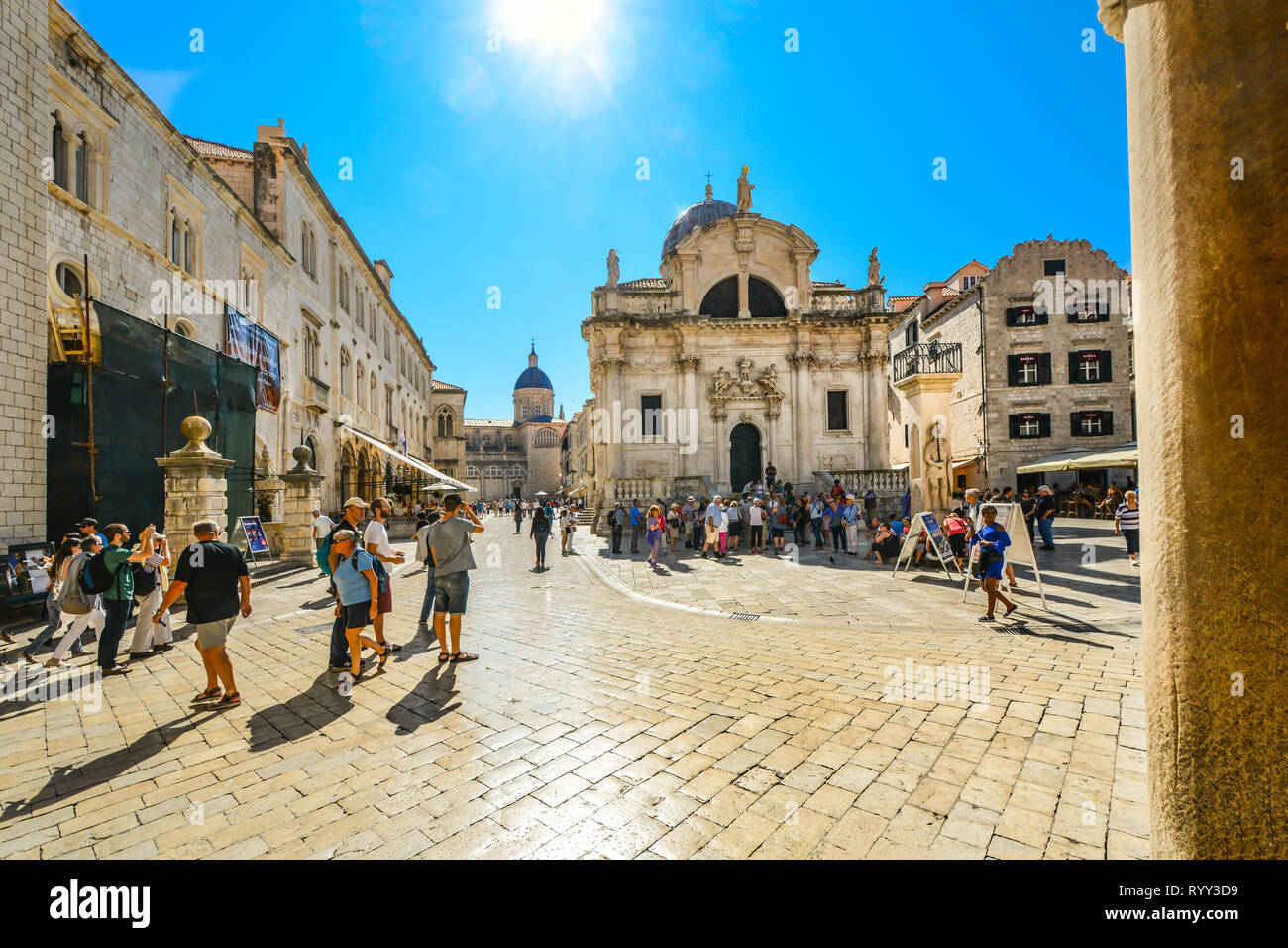 Tourists walk under the hot summer sun in the stradun or placa in Old Town Dubrovnik with St Blaise Church and the Dubrovnik Cathedral in view Stock Photo