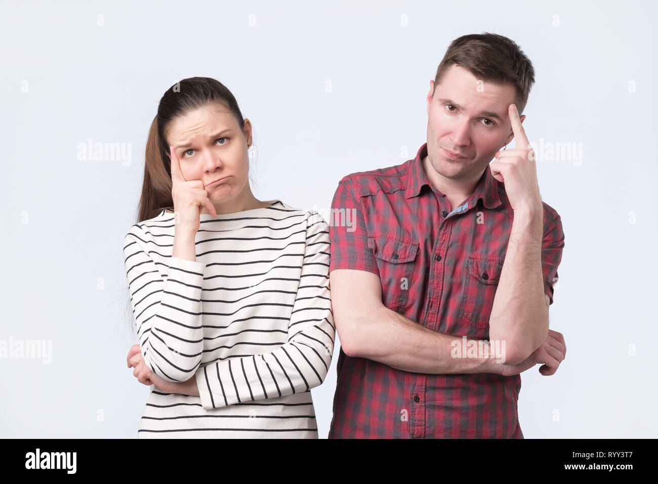 Attractive young couple standing side by side thinking puzzled - Stock Image
