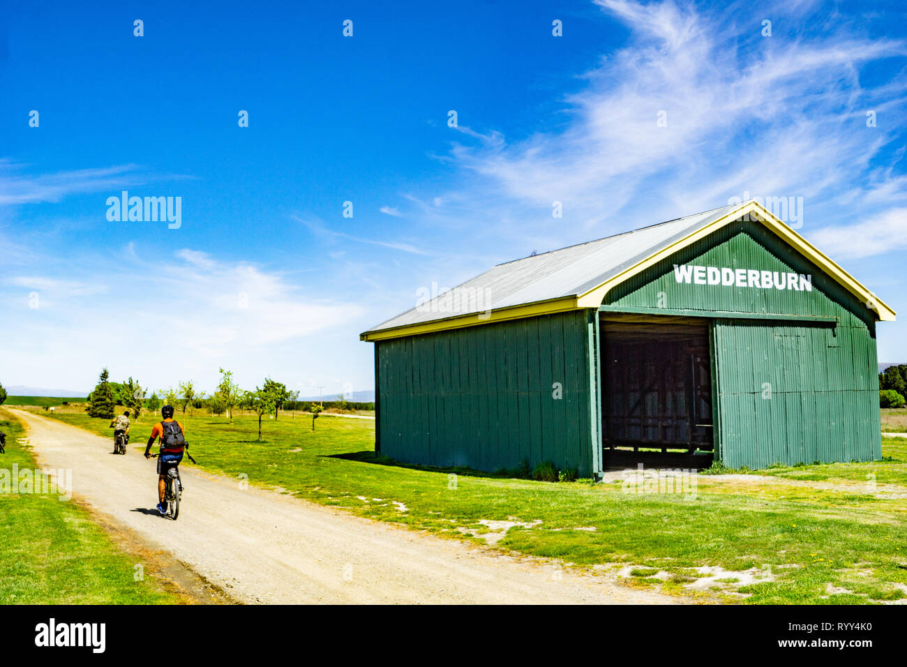 WEDDERBURN NEW ZEALAND - OCTOBER 22 2018;  on Central Otago Rail Trail cyclists passing old landmark green rail shed - Stock Image