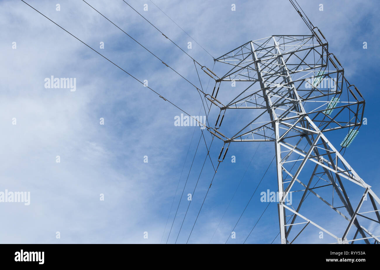 High voltage power lines going through a tower - Stock Image