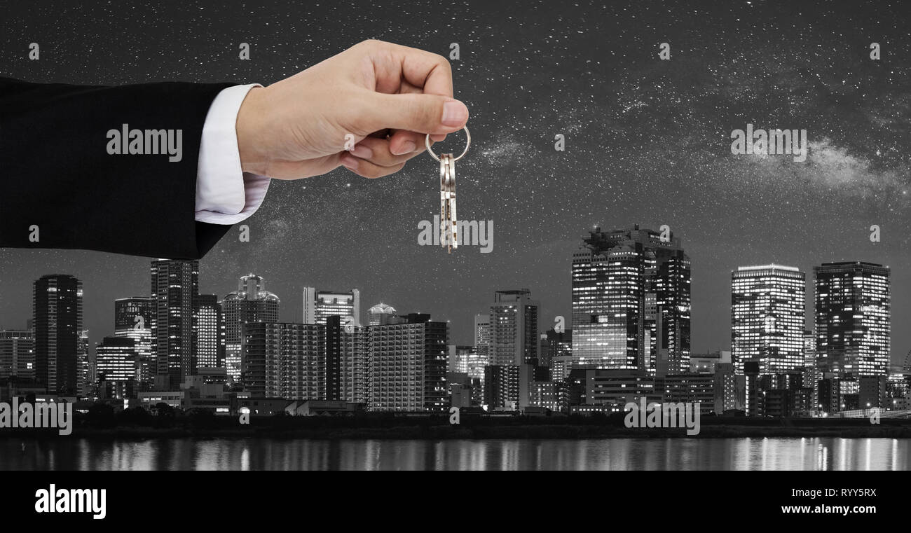 Real estate business, residential rental and investment. Businessman handover keys, with city at night in Japan backgrounds Stock Photo