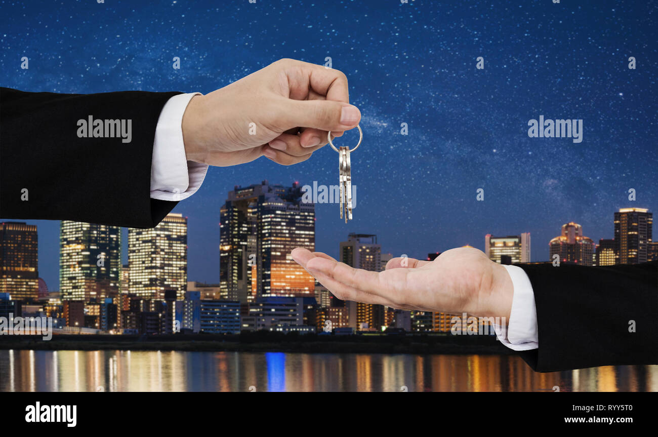 Real estate business, residential rental and investment. Businessman handover keys, with city at night in Japan backgrounds - Stock Image