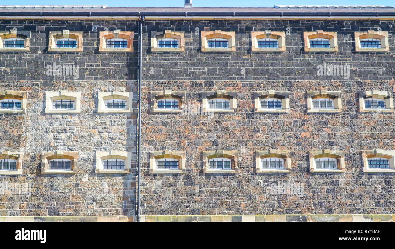 Many small windows on the jail building in Belfast city in Ireland - Stock Image