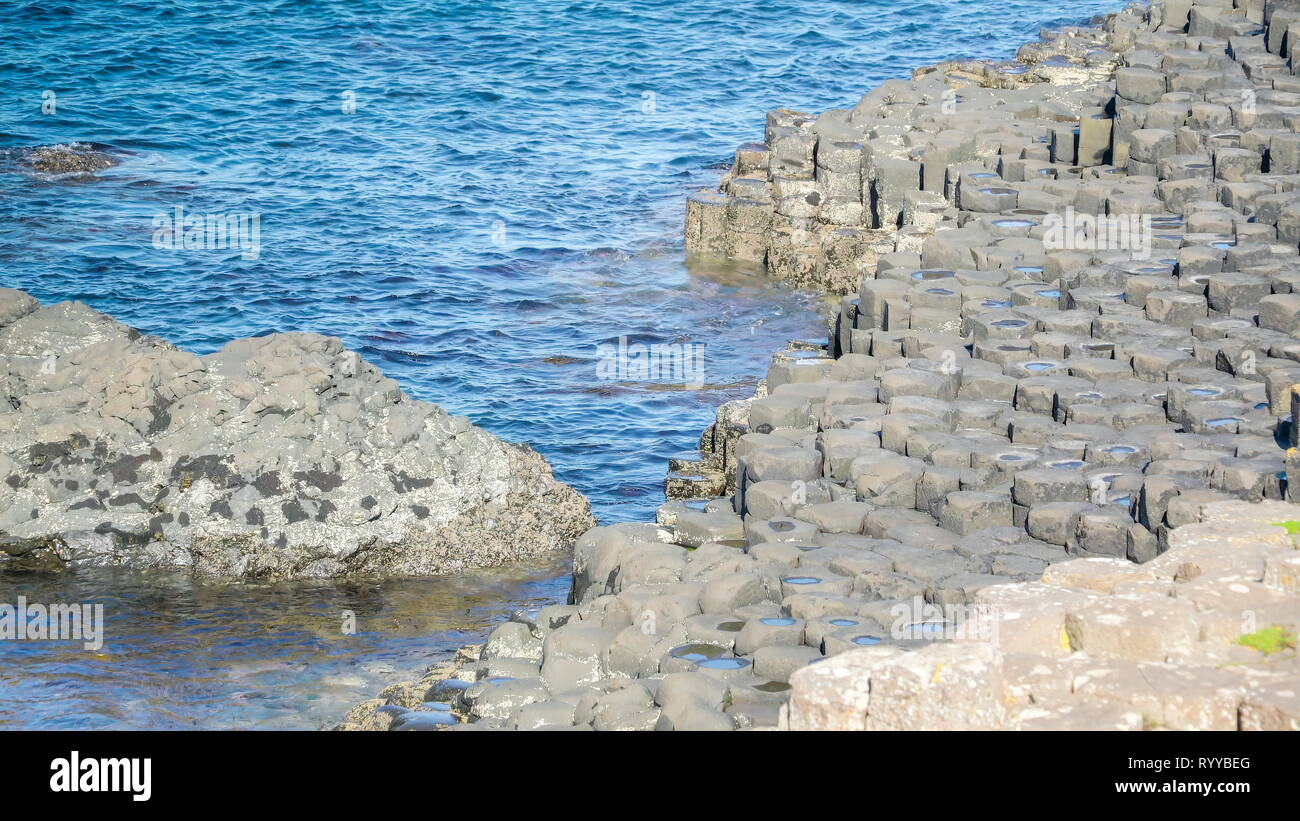 The rock basalt and the sea water colliding found in the Giants Causeway in Northern Ireland Stock Photo