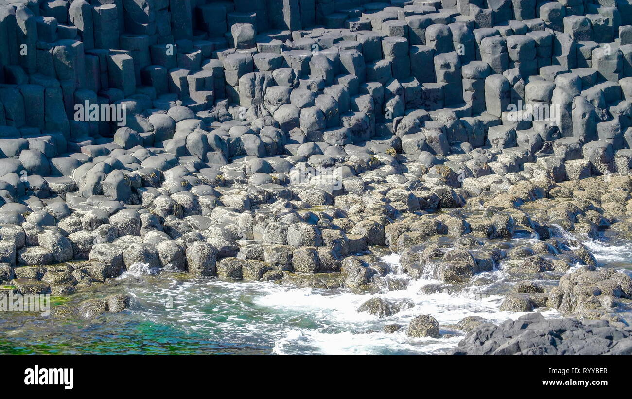 Rocks on the seashore in the Giants Causeway with the splash of waves coming from the sea Stock Photo