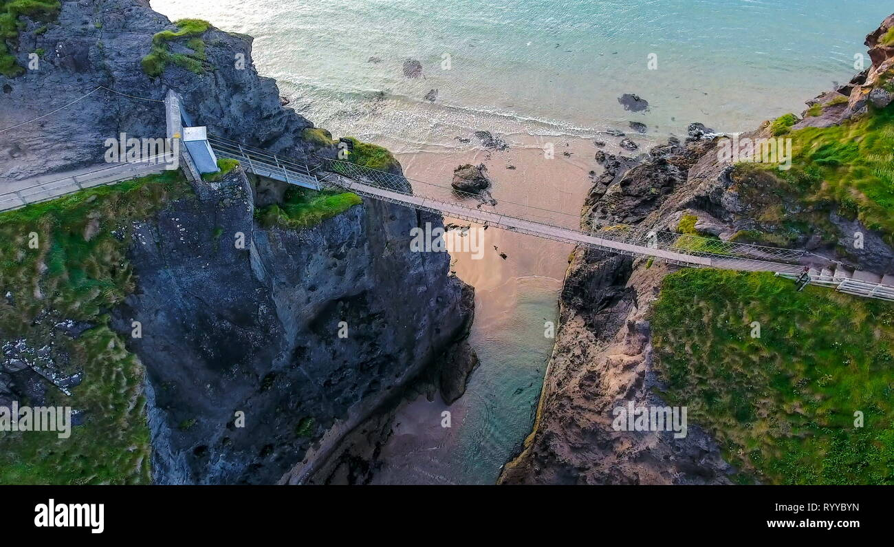 Aerial shot of the long rope bridge in Carrick-a-Rede. The bridge links the mainland to the tiny island of Carrickarede. - Stock Image