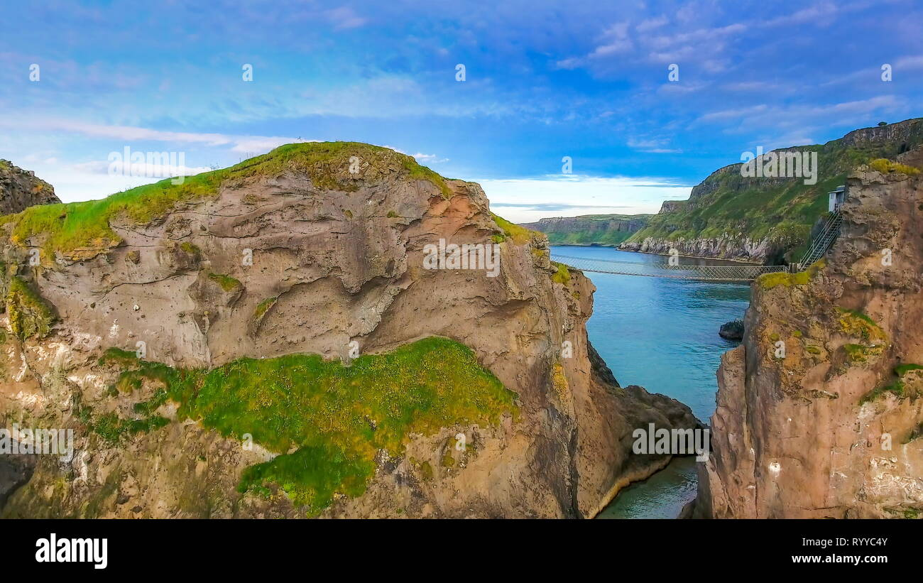 The amazing landscape view of the Carrick-a-Rede Rope Bridge and the big blue ocean on the islands in Ireland - Stock Image