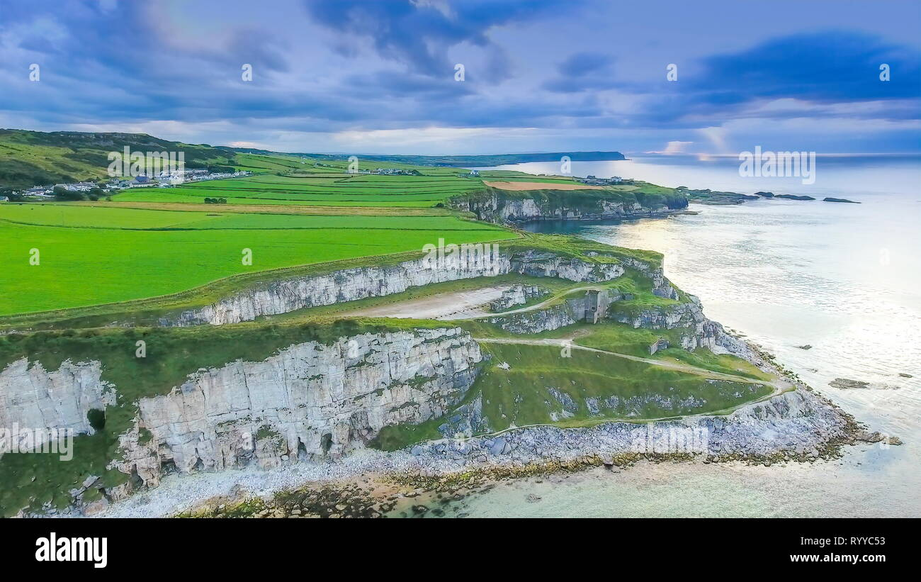 The mainland and the cliff in Carrick-a-Rede the green mainland where tourists visits to enoy the scenery of the beach in Ireland - Stock Image
