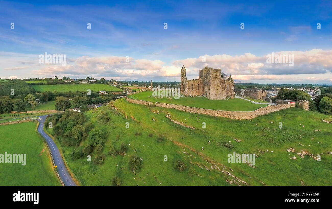 The green field and the hill in Rock of Cashel where the old ruined castle is being located with the blue sky and the white clouds on a fine day in Ir - Stock Image
