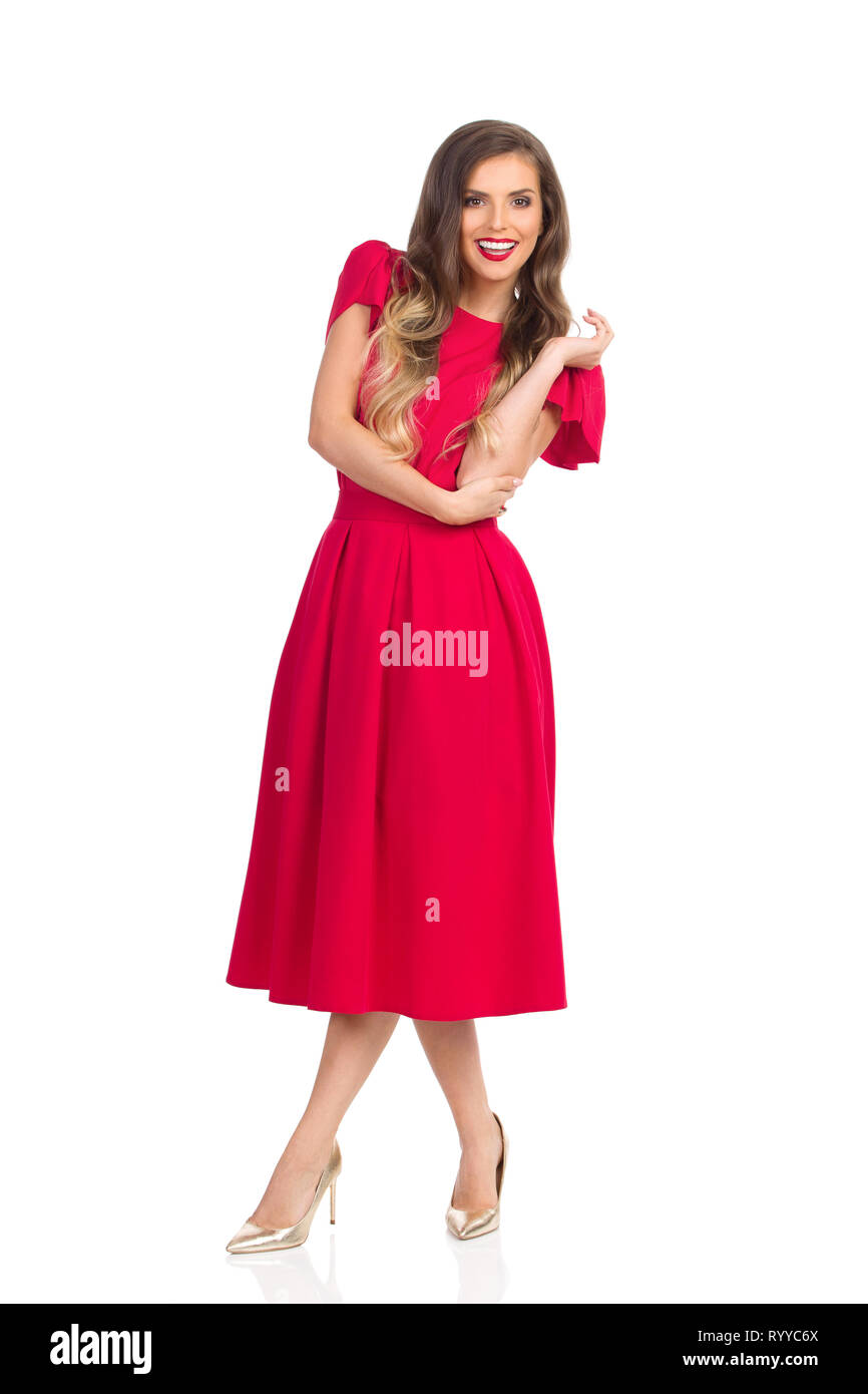 Smiling beautiful young woman in red dress and high heels is standing with legs crossed and looking at camera. Full length studio shot isolated on whi - Stock Image