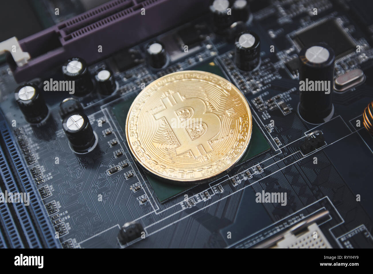 Golden Bitcoin coins on Motherboard, miner with circuit