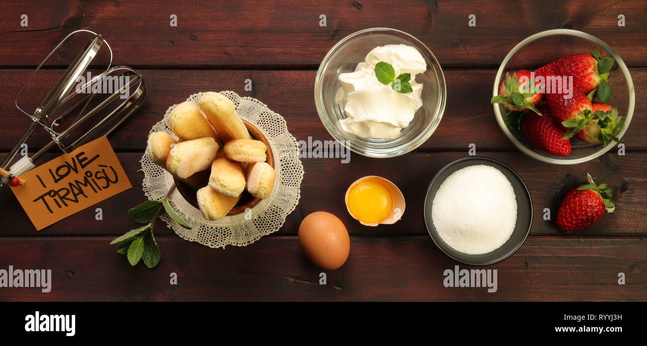 Ingredients for strawberry tiramisu with tag on wooden table - Stock Image