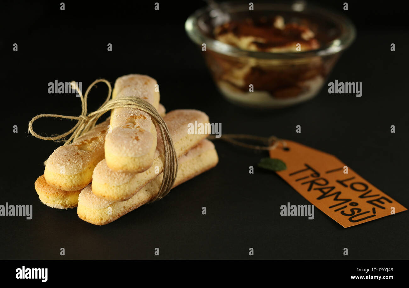 Italian savoiardi ladyfingers biscuits on dark background - Stock Image