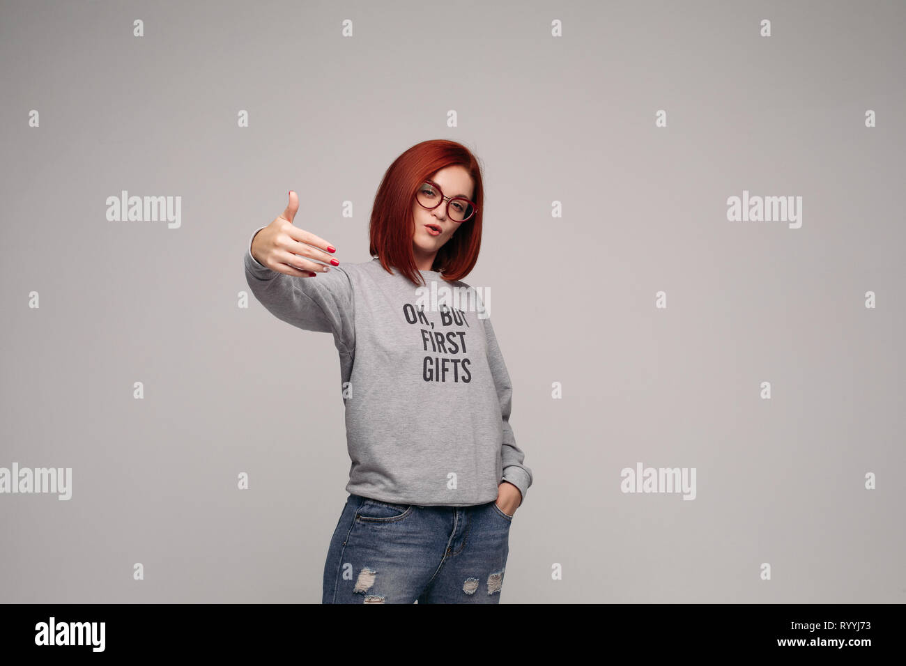 Swag and confident red haired girl in jeans and sweatshirt