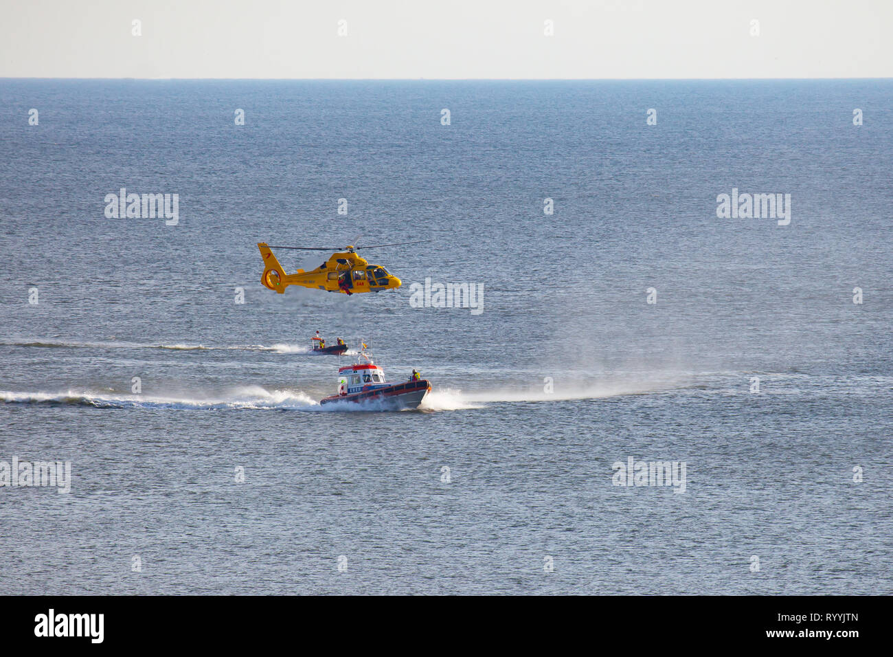 a helicopter of the dutch coastgard is abseiling a man over the sea during a rescue drill Stock Photo