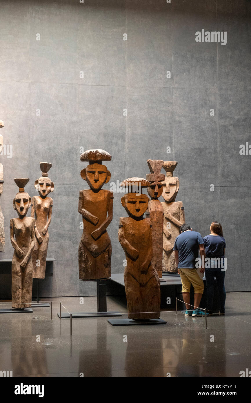A couple looks at a display of Chemamulles, or wooden Mapuche funerary statues, in the Museo Chileno de Arte Precolombino in Santiago, Chile. - Stock Image