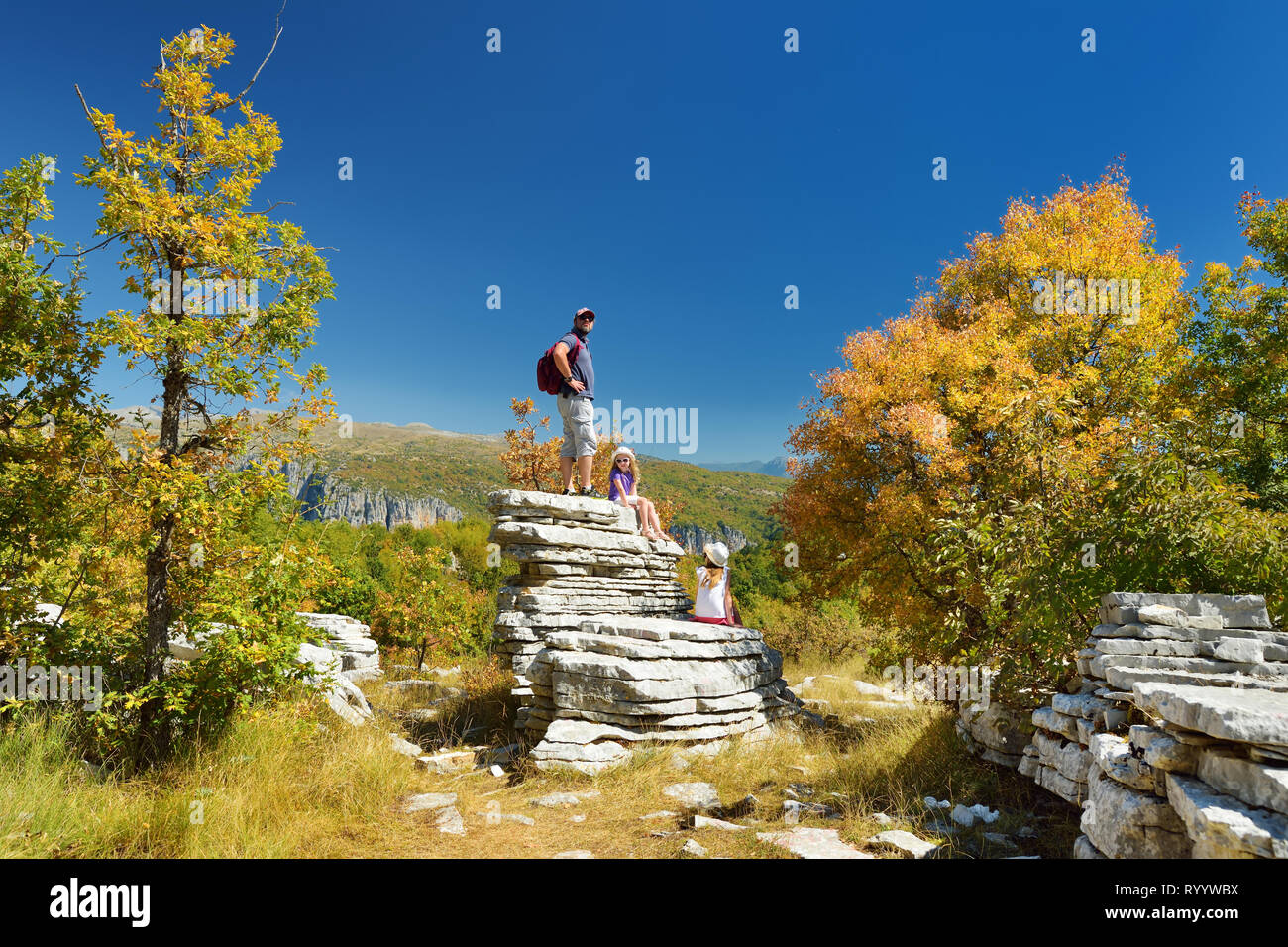 Father and kids exploring Stone forest, natural rock formation, created by multiple layers of stone, located near Monodendri village in Zagori region, - Stock Image