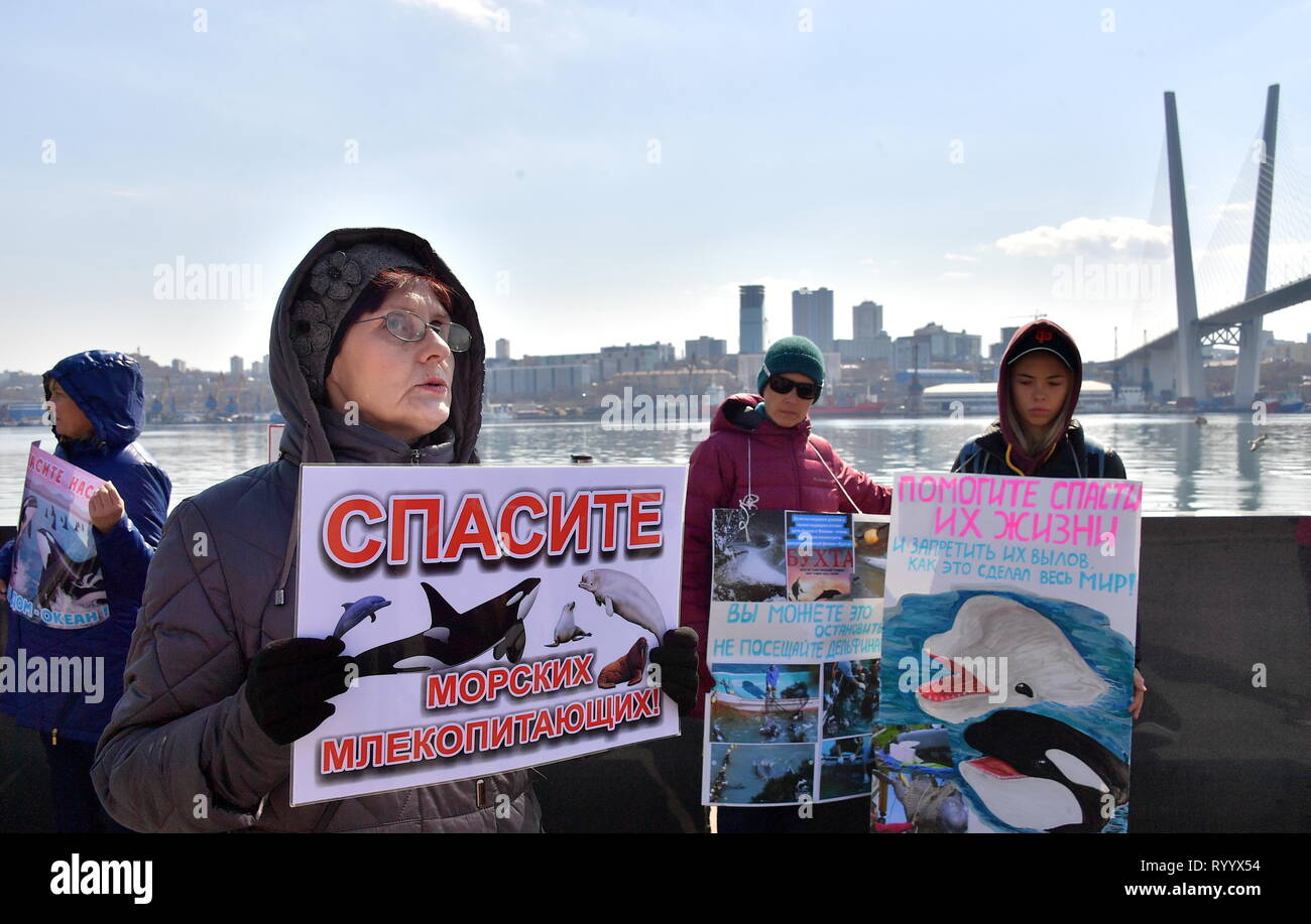 VLADIVOSTOK, RUSSIA - MARCH 16, 2019: People take part in a rally to free beluga and orca whales kept in a 'whale prison' off the Russian Pacific coast. A marine containment facility branded a 'whale prison' was discovered in the Srednyaya Bay in Primorye Territory in 2018; 90 belugas and 11 orcas were captured in the 'whale prison' to be sold to Chinese amusement parks; later, three beluga whales and one orca disappeared. Russian police and prosecutors are carrying out a criminal investigation. Yuri Smityuk/TASS - Stock Image