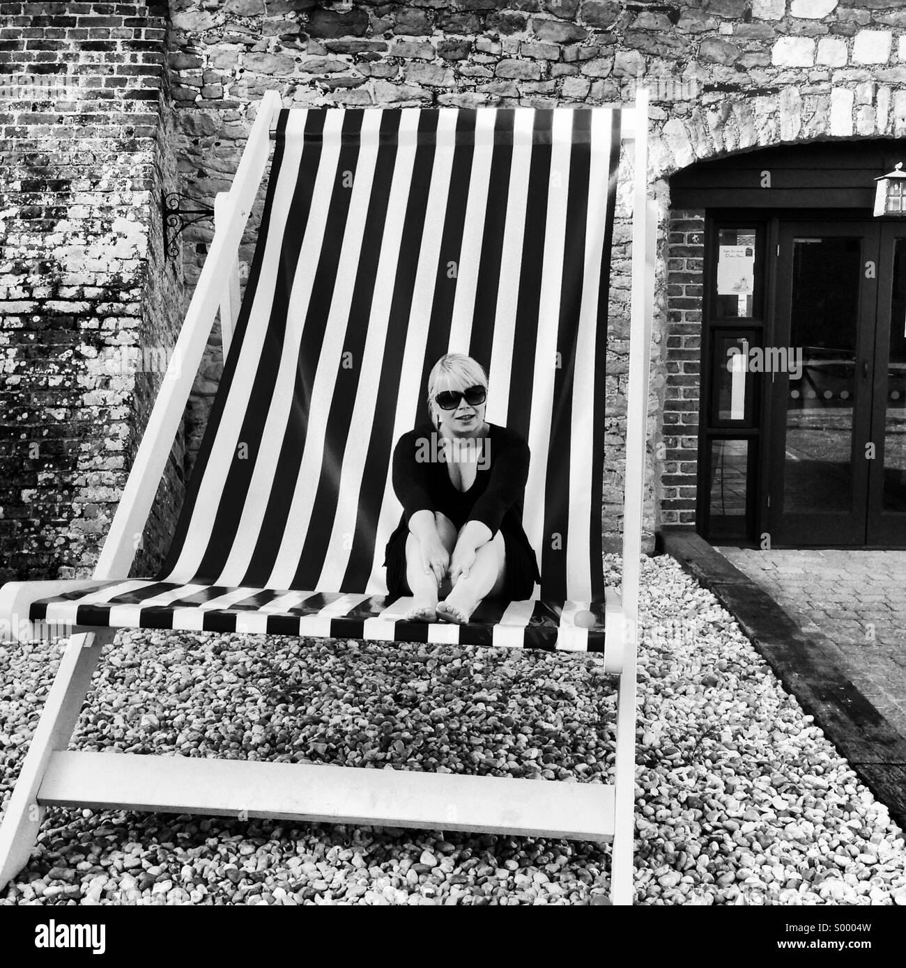 Girl sitting in big stripy deck chair - Stock Image