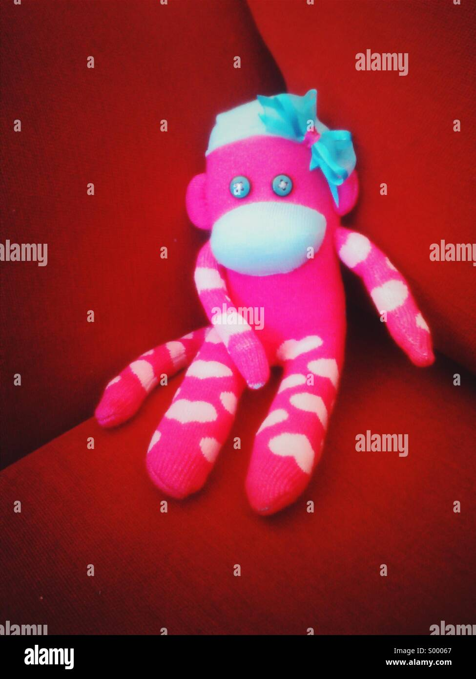 Pink sock monkey laid back on red sofa - Stock Image