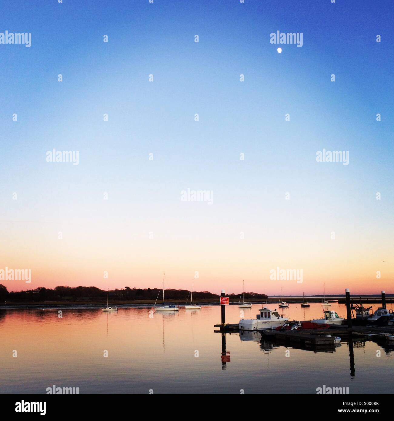 Sunset at the Royal Yacht Club at Lymington.  The moon rises as the sun sets and the water turns to glass. Sailboats - Stock Image