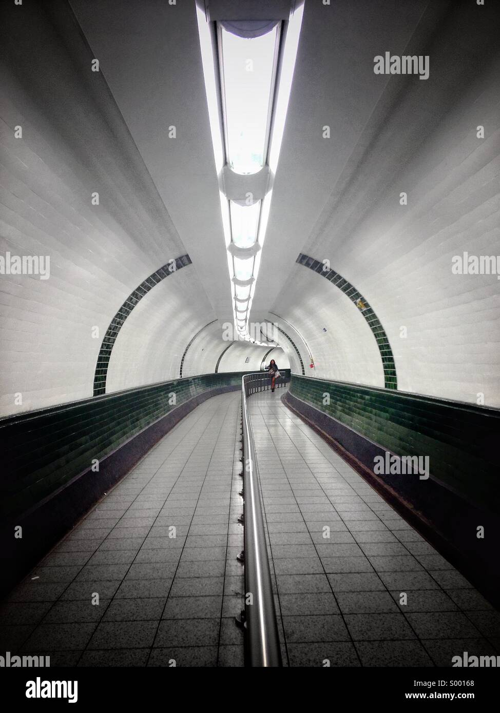 Woman walking through tunnel. - Stock Image