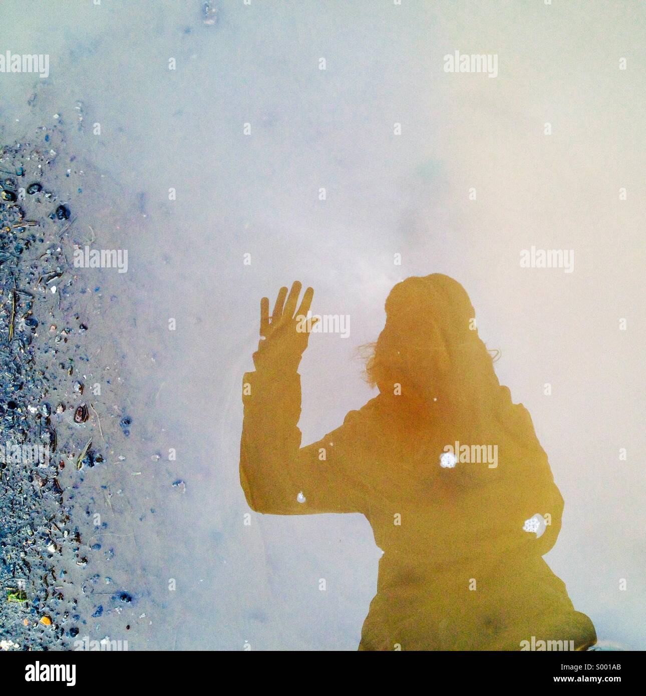 Waving, reflection of person in puddle - Stock Image