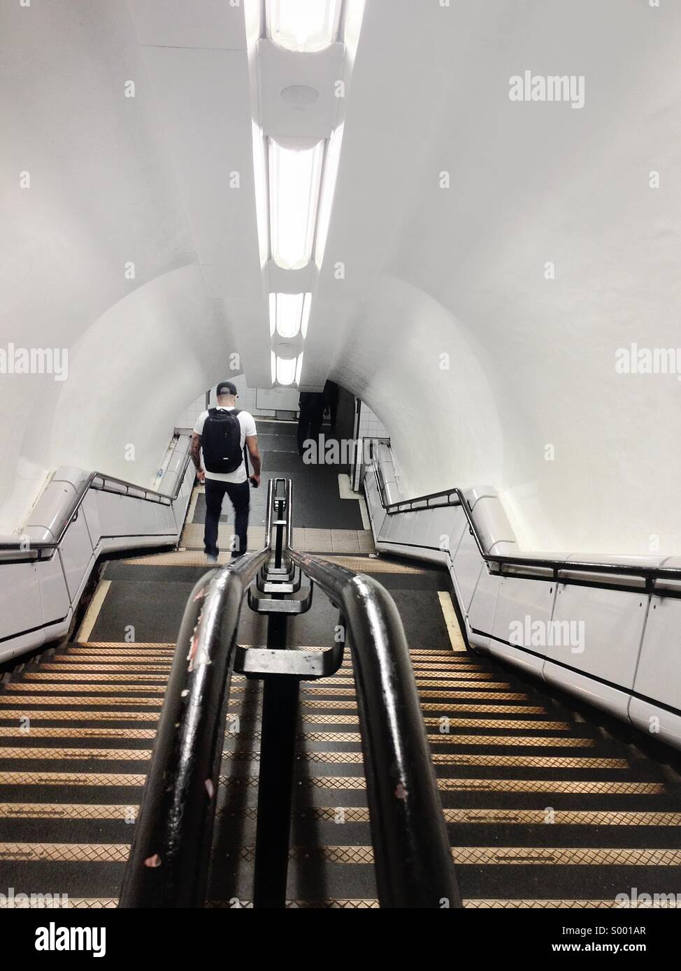 Man going down the stairs. London Underground. - Stock Image
