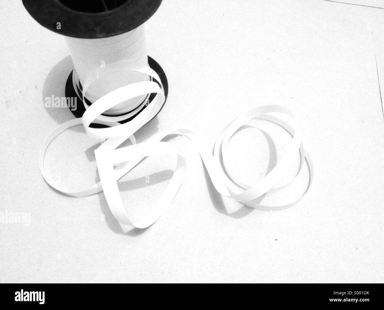 White gift ribbon and spool on white background - Stock Image
