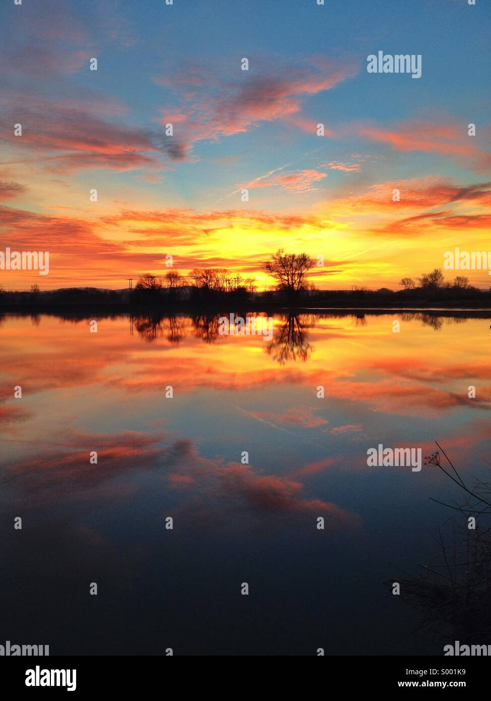 Sunrise over a river - Stock Image