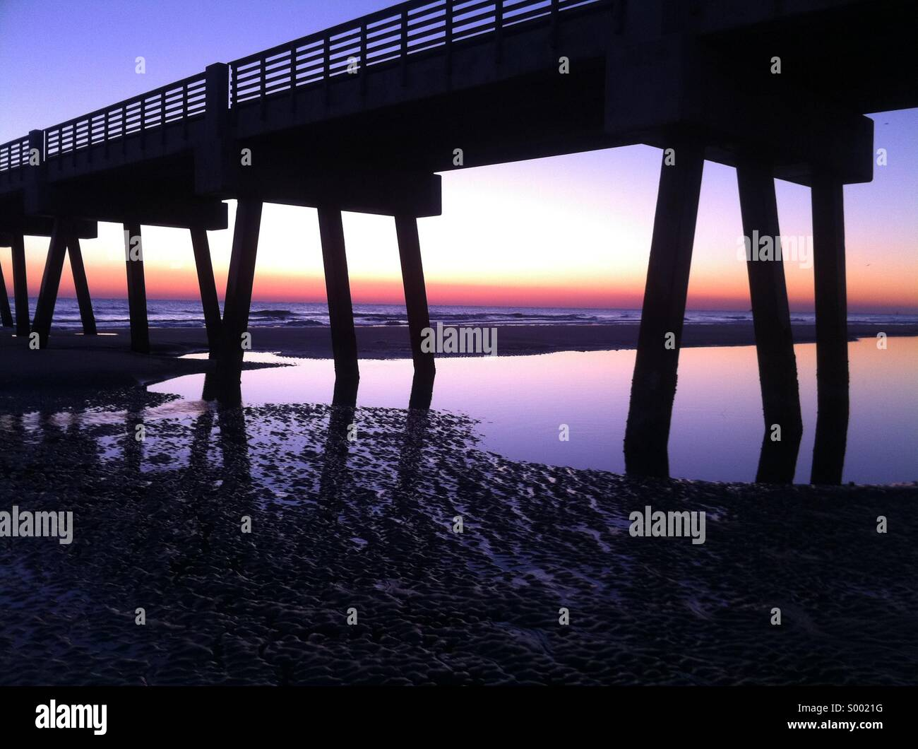 Pooled water reflects a vibrant sunrise sky at Jacksonville Beach Pier in Jacksonville Beach, Florida. USA. Stock Photo