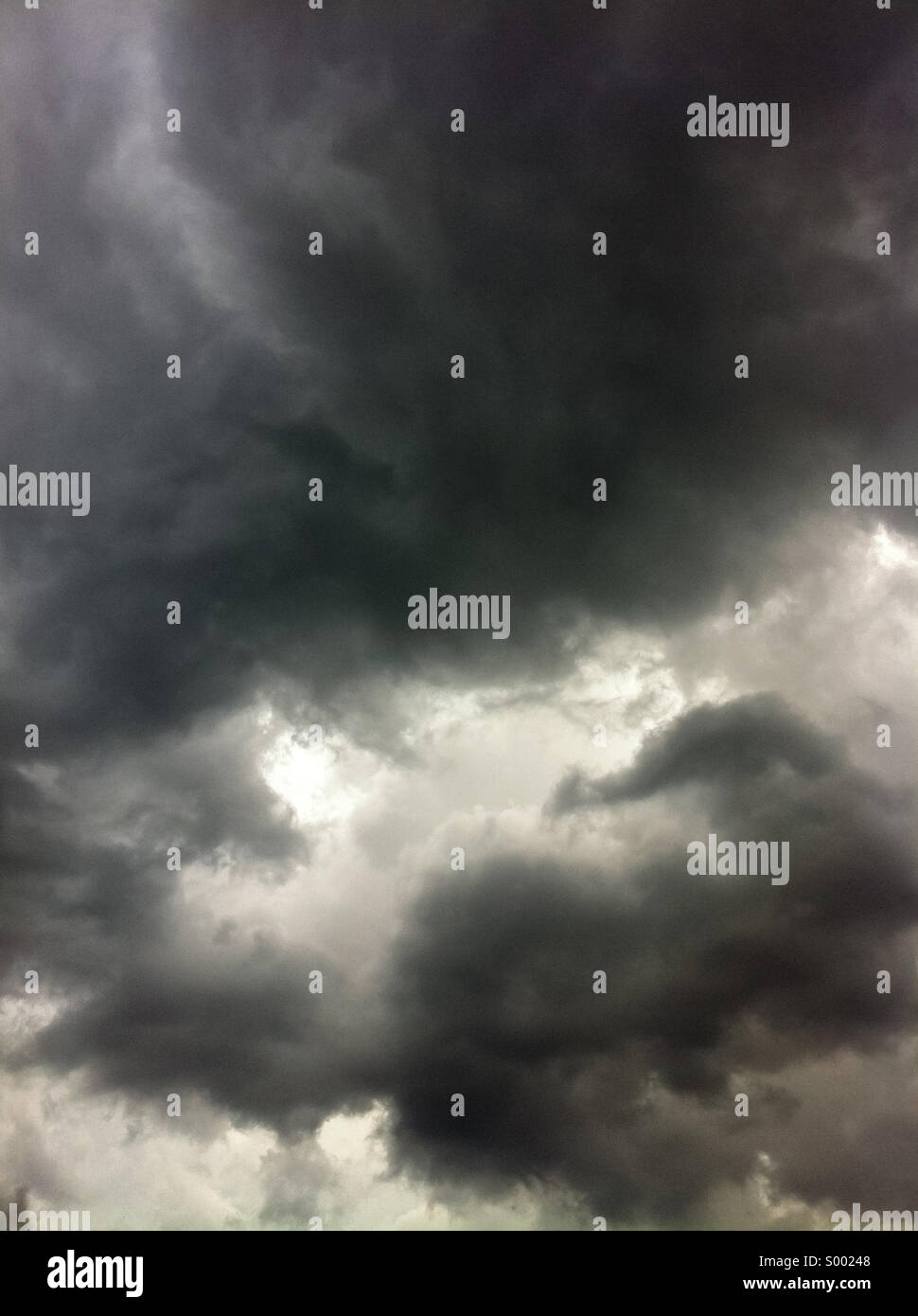 Sunlight peeks through dark, foreboding clouds in a violent, stormy sky. - Stock Image