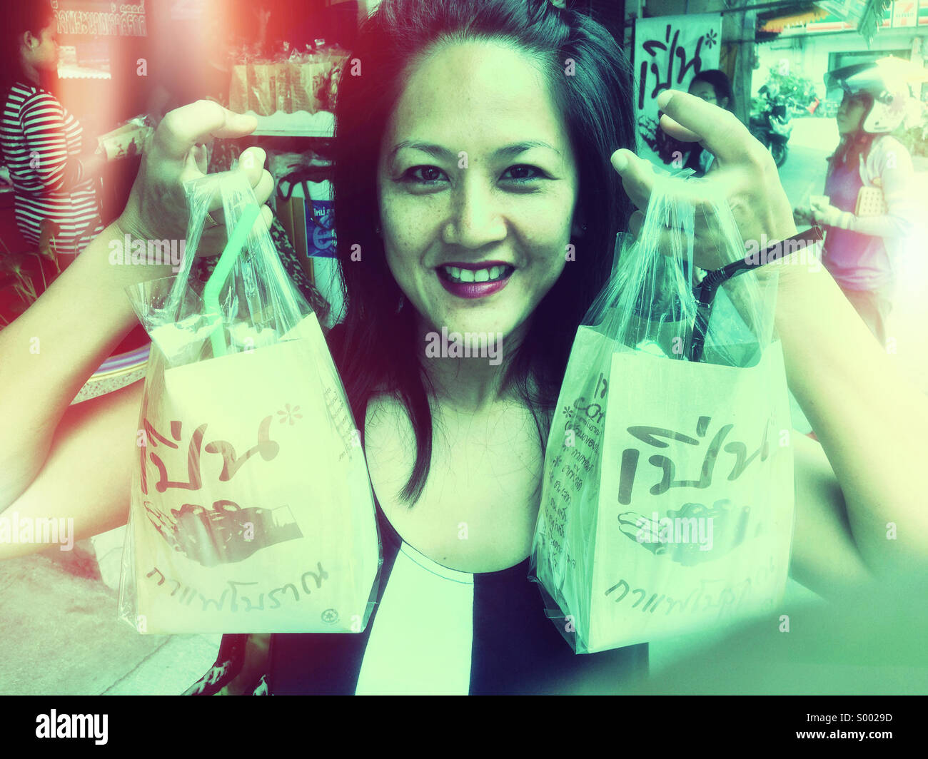 Thailand girl with Thai coffee purchase. - Stock Image