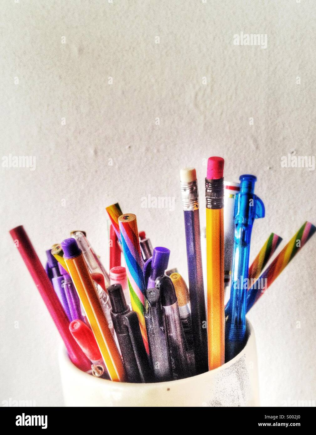 Colorful pens in jug - Stock Image