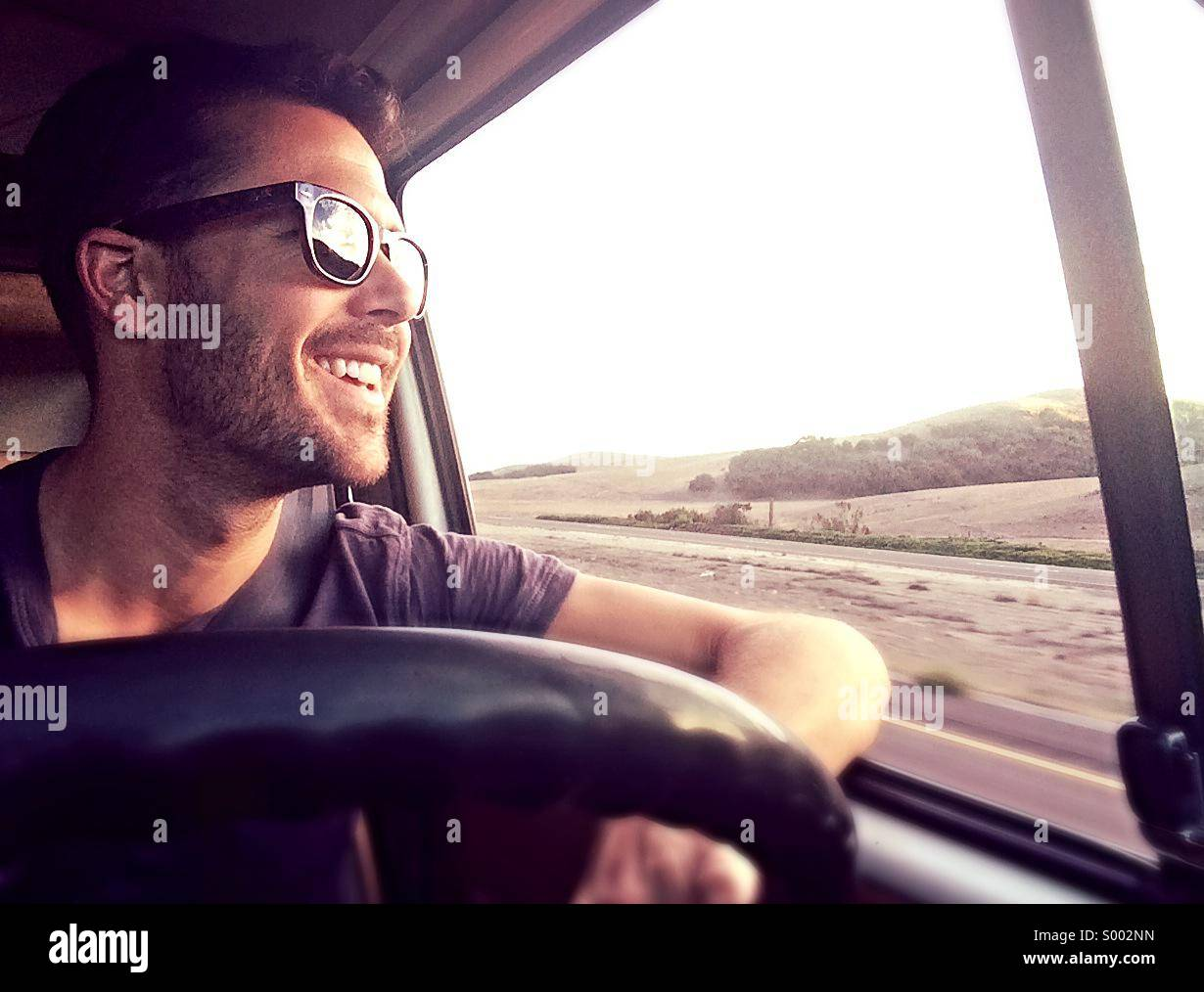 Young man drives VW Westfalia down highway 101 in California, USA Stock Photo