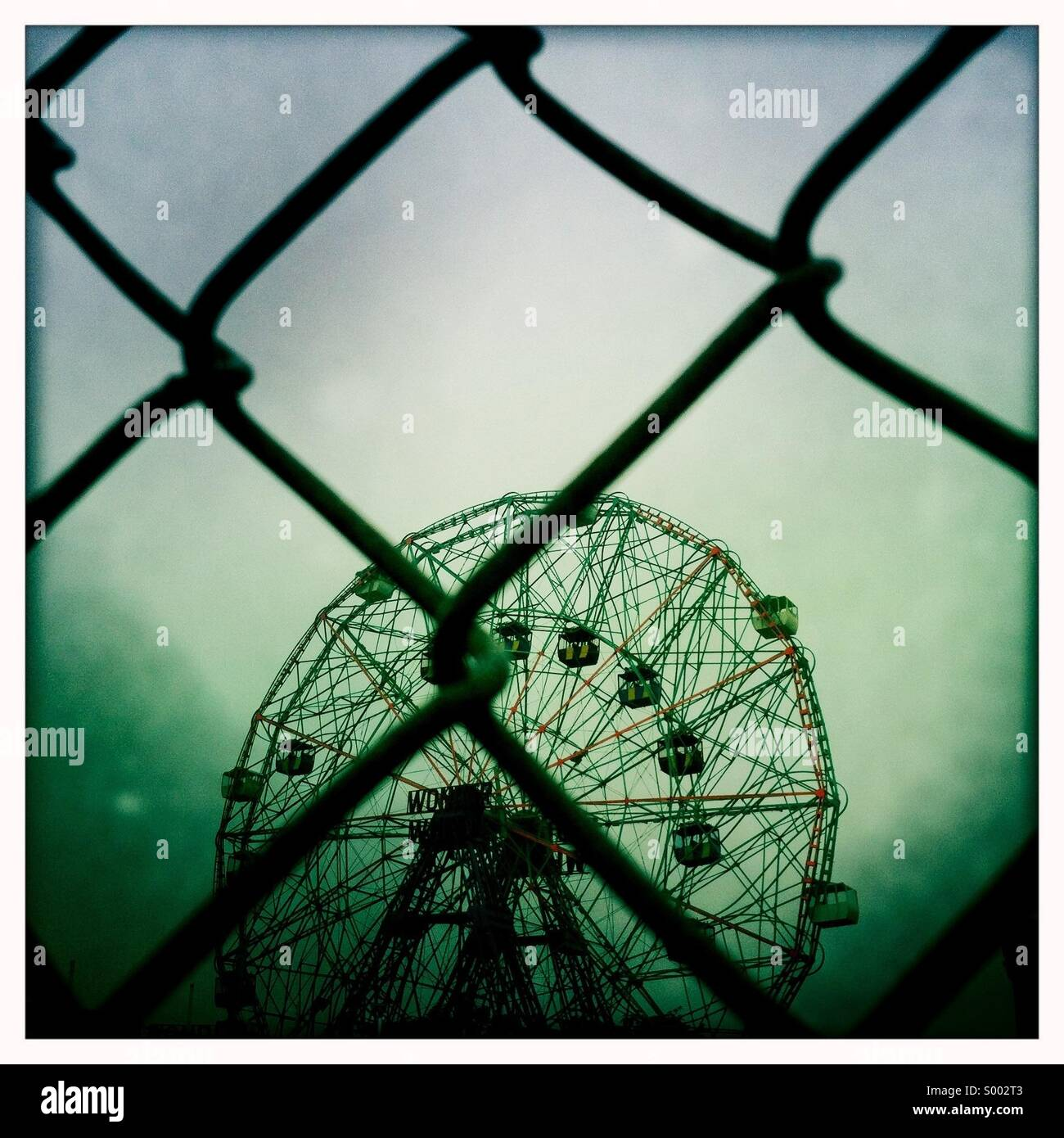 Amusement park Ferris wheel closed behind a gate - Stock Image